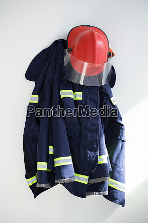 protective workwear hanging against white wall