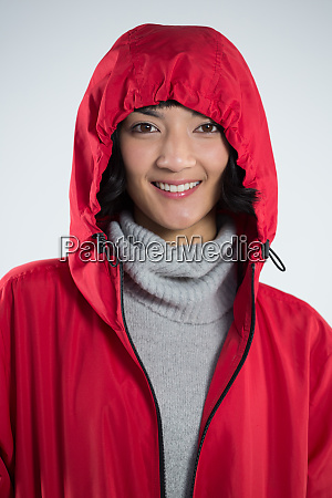 smiling woman in hooded jacket standing