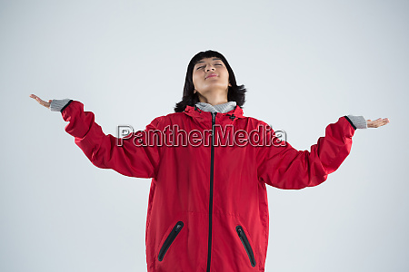 blissful woman standing with arms outstretched