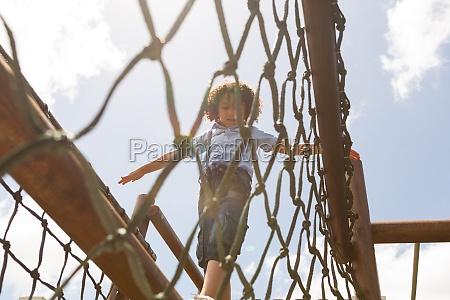 schoolgirl walking on net bridge in