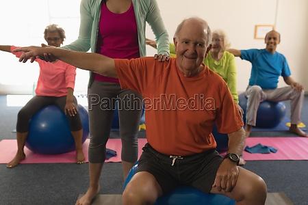 female trainer assisting senior man in