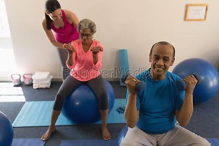 female trainer assisting senior woman in