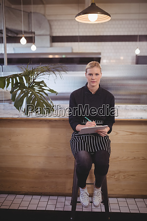 portait of confident young waitress sitting
