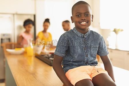 happy african american boy sitting on