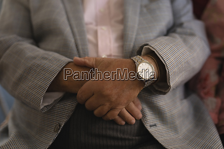 senior man with folded hands at