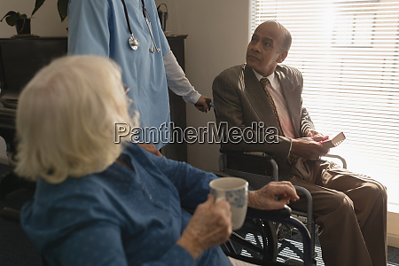 disable senior couple talking with doctor