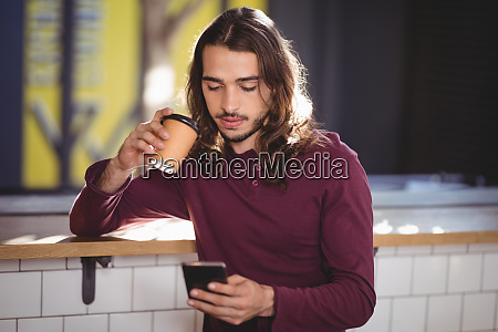 young handsome man drinking coffee while