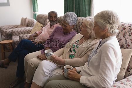 senior people having coffee in living
