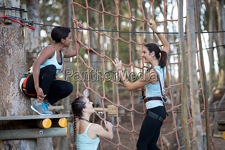 friends climbing a net during obstacle