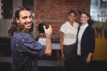 smiling young photographer photographing female colleagues
