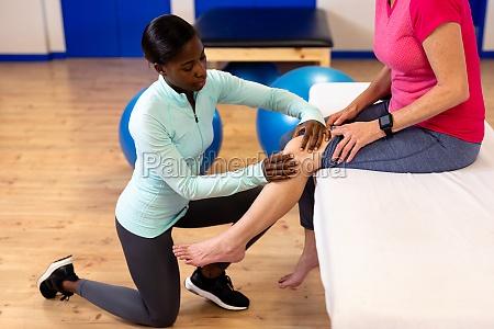 female physiotherapist giving leg massage to