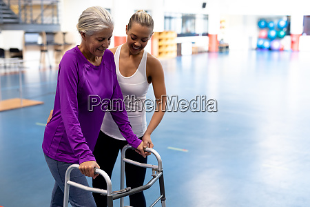 female physiotherapist helping disabled senior woman
