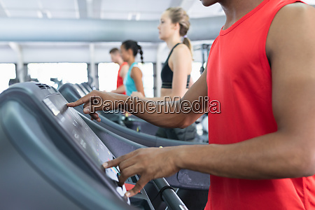 fit man operating treadmill while exercising