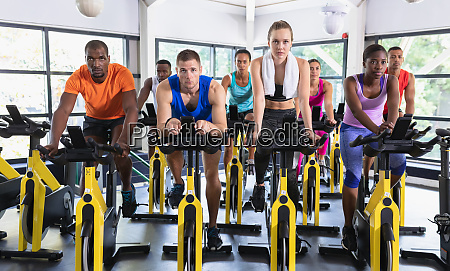 fit people exercising on exercise bike