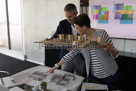 business people discussing over blueprint in