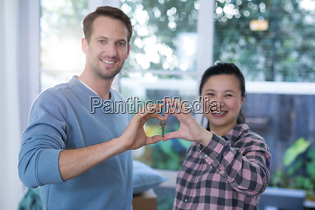 smiling couple making heart shape with