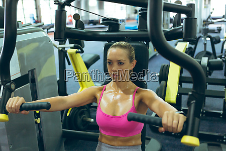 female athlete exercising with chest press