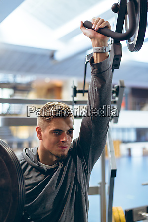 man exercising with shoulder machine in