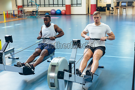 male athletes exercising with rowing machine
