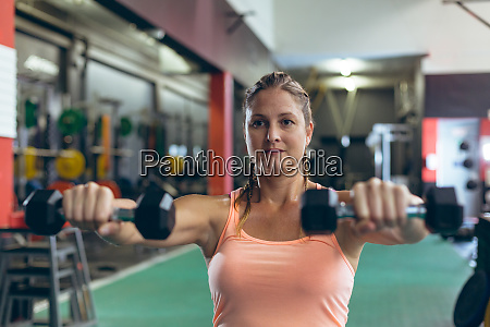 female athlete exercising with dumbbell in
