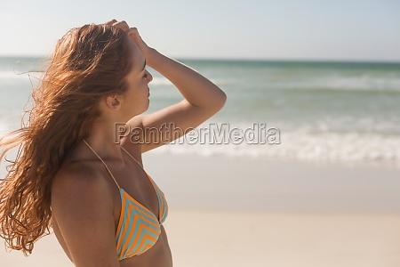 young caucasian woman in bikini caressing