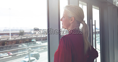 thoughtful senior businesswoman looking through window