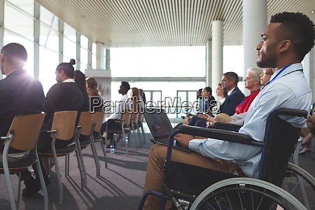 disabled young businessman using laptop during