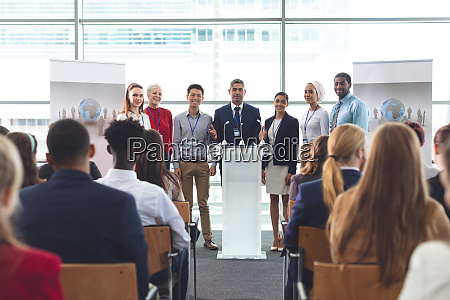 businessman standing at podium with colleagues
