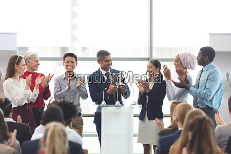 businessman holding award at podium with