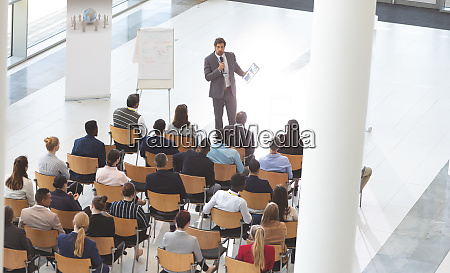 businessman speaking in front of business