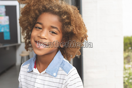 african ethnicity schoolboy smiling while looking