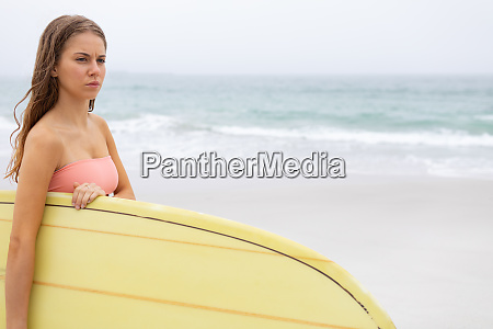 woman holding her surfboard on the