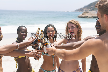 multi ethnic group of friends toasting