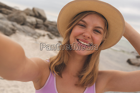 caucasian woman with hat standing at