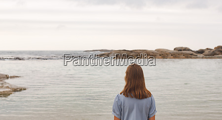 young caucasian woman standing at beach