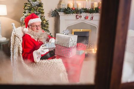 santa, claus, looking, at, gift, boxes - 27604449