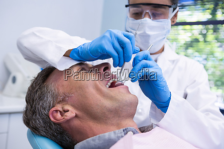 happy man receiving dental treatment by