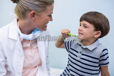 boy holding toothbrush while looking at
