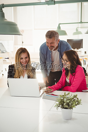executives discussing over laptop at desk