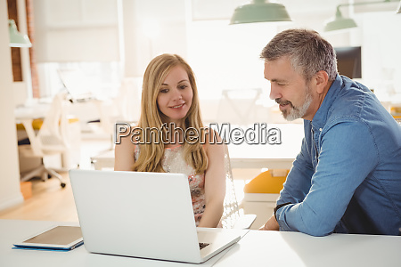 executives discussing over laptop in office