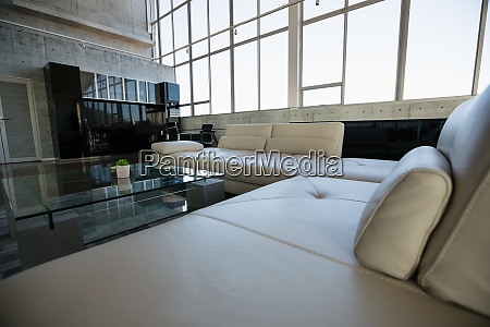 glass table by empty white sofa