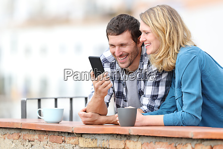 happy adult couple checking smart phone