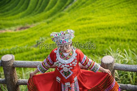 woman in folk costume longji rice