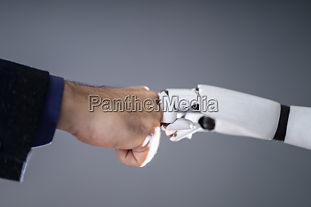 robot and human hand making fist