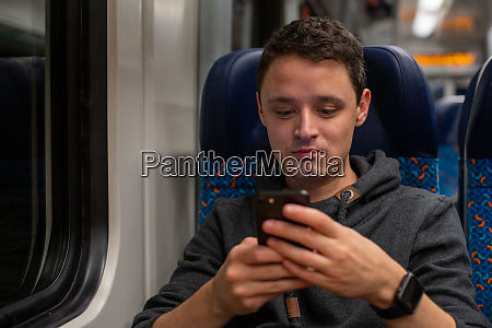 young man on the train reads