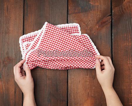 hands hold white red checkered kitchen