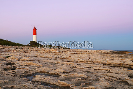 rocky landscape with lighthouse over clear