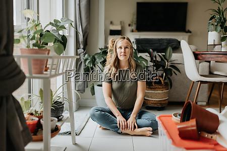 woman sitting cross legged in room