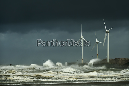 wind turbines battered by large waves