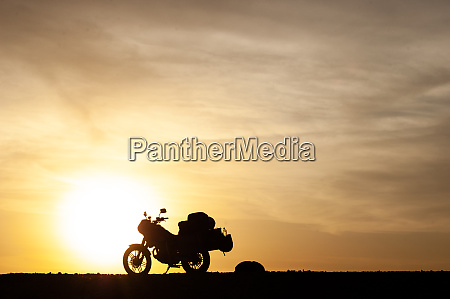 silhouetted touring motorcycle at sunset
